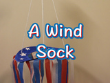 Learn how to make a patriotic wind sock. You will need: paper plate, blue plate, cut outs of white stars, ribbon/tissue (red, white, and blue), scissors, glue, string, and a while puncher.